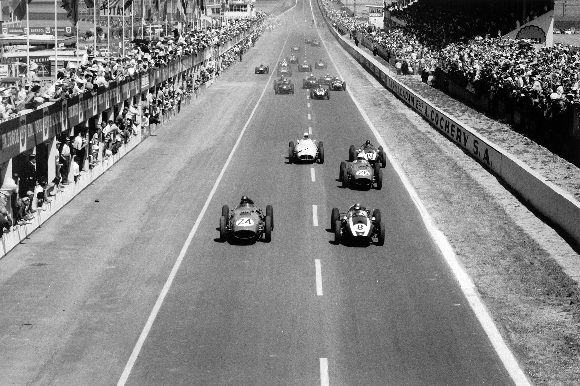 Tony Brooks, #24 Ferrari Dino 246 and Jack Brabham, Cooper T51-Climax, lead at the start.