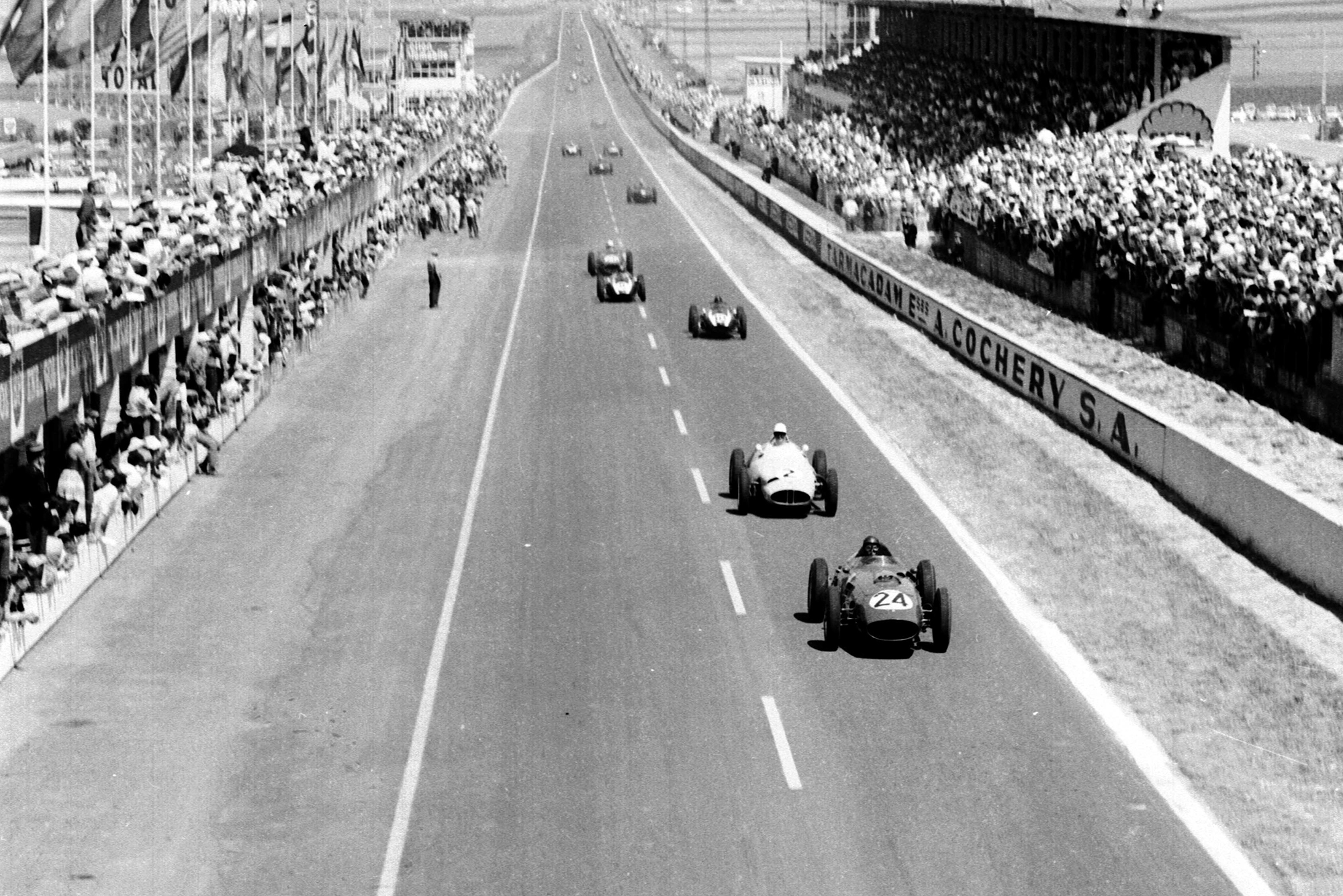 Tony Brooks (Ferrari Dino 246) leads Stirling Moss (BRM P25) and the field past the grandstands and pits.