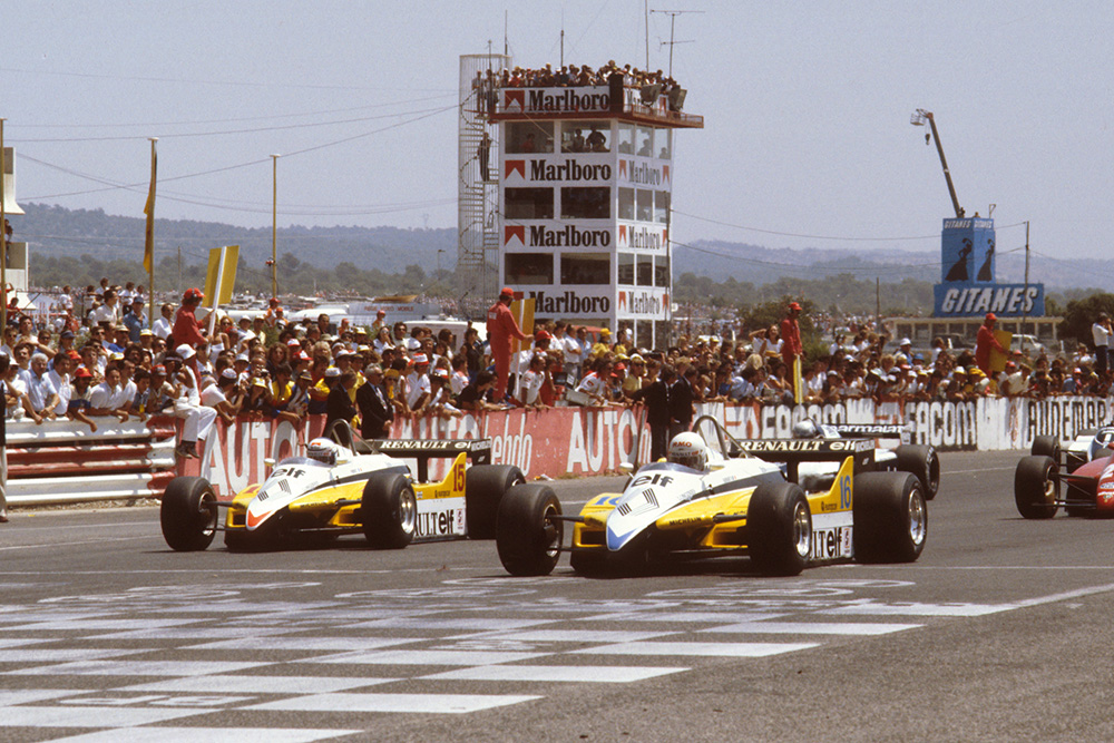 Rene Arnoux and Alain Prost (both Renault RE30B's) lead the rest of the field away from the front row at the start.