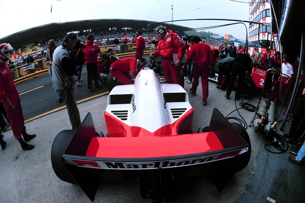 Alain Prost's Mclaren MP4-2C, Jo Ramirez leaning over talking to Prost (left of car).