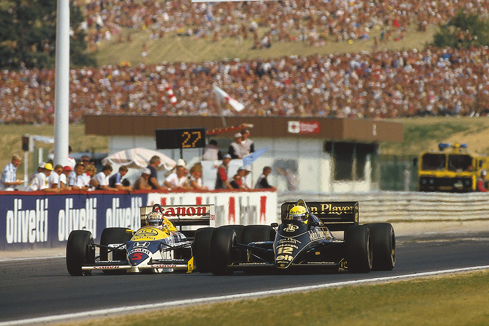 Ayrton Senna (Lotus 98T Renault) overtakes Nigel Mansell (Williams FW11 Honda). They finished in 2nd and 3rd positions respectively.
