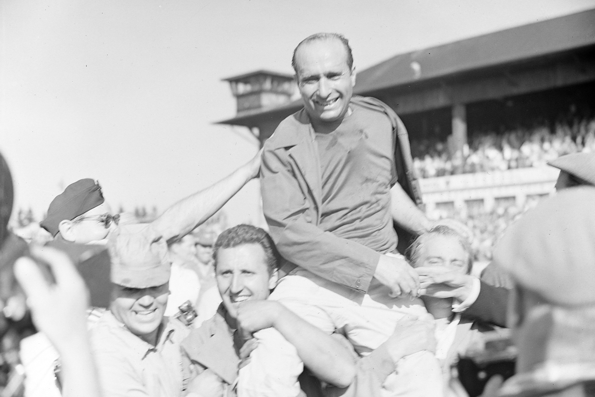 Juan Manuel Fangio celebrates with his team after winning the 1957 German Grand Prix and his fifth F1 title, Nurburgring