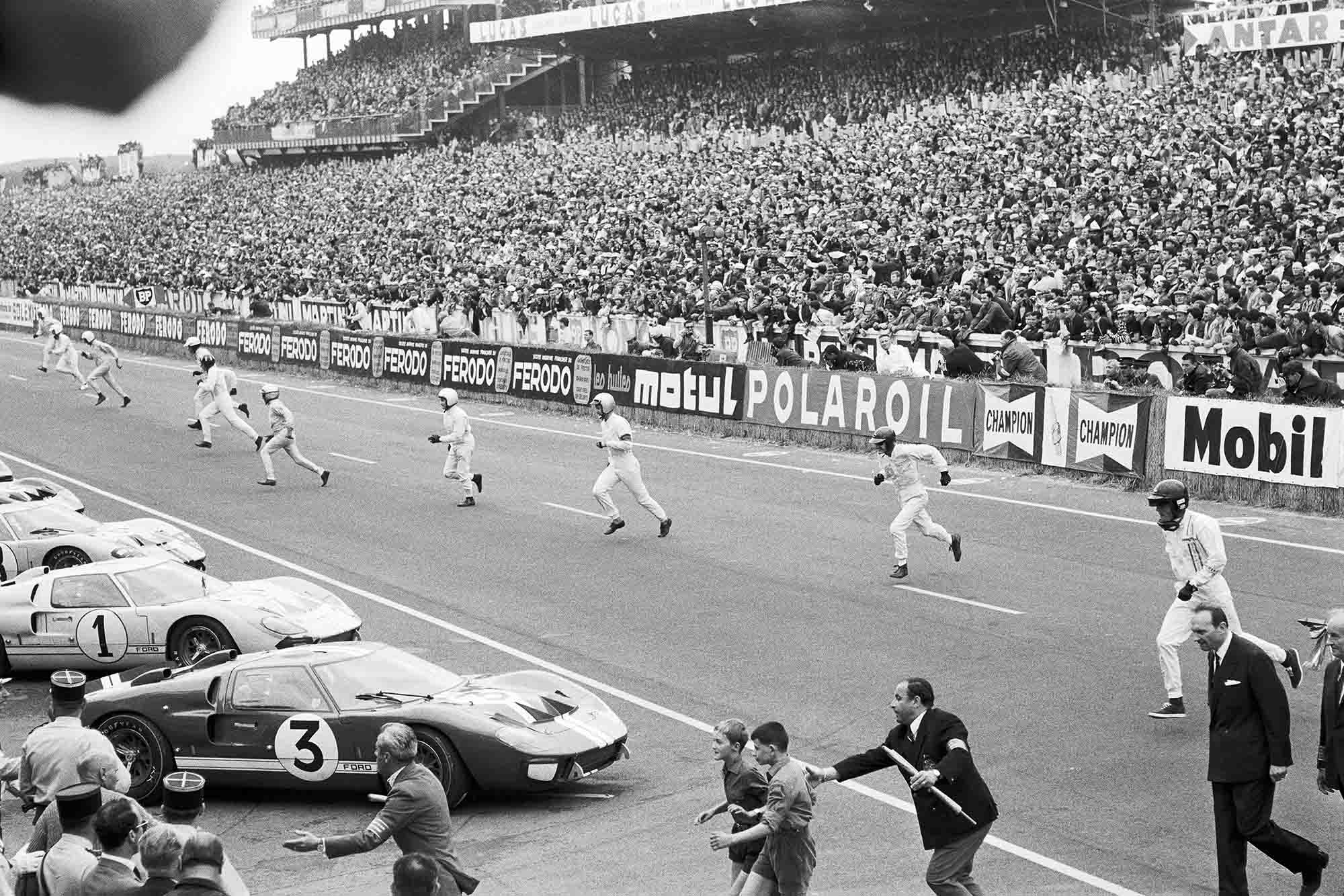 Drivers run to their cars at the start of 1966 Le Mans, with Dan Gurney on the right heading to his Ford GT40 MkII, followed by Ken Miles, John Whitmore, Bruce McLaren, Pedro Rodriguez, Graham Hill, Mike Parkes and Jean Guichet.