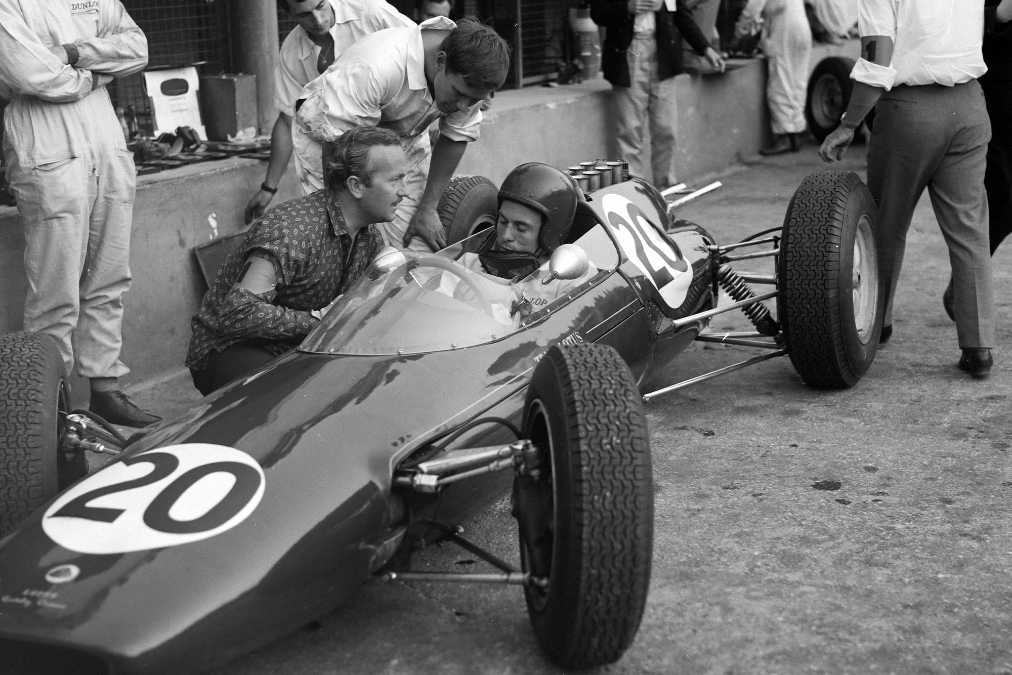 Jim Clark and Colin Chapman converse in the pitlane