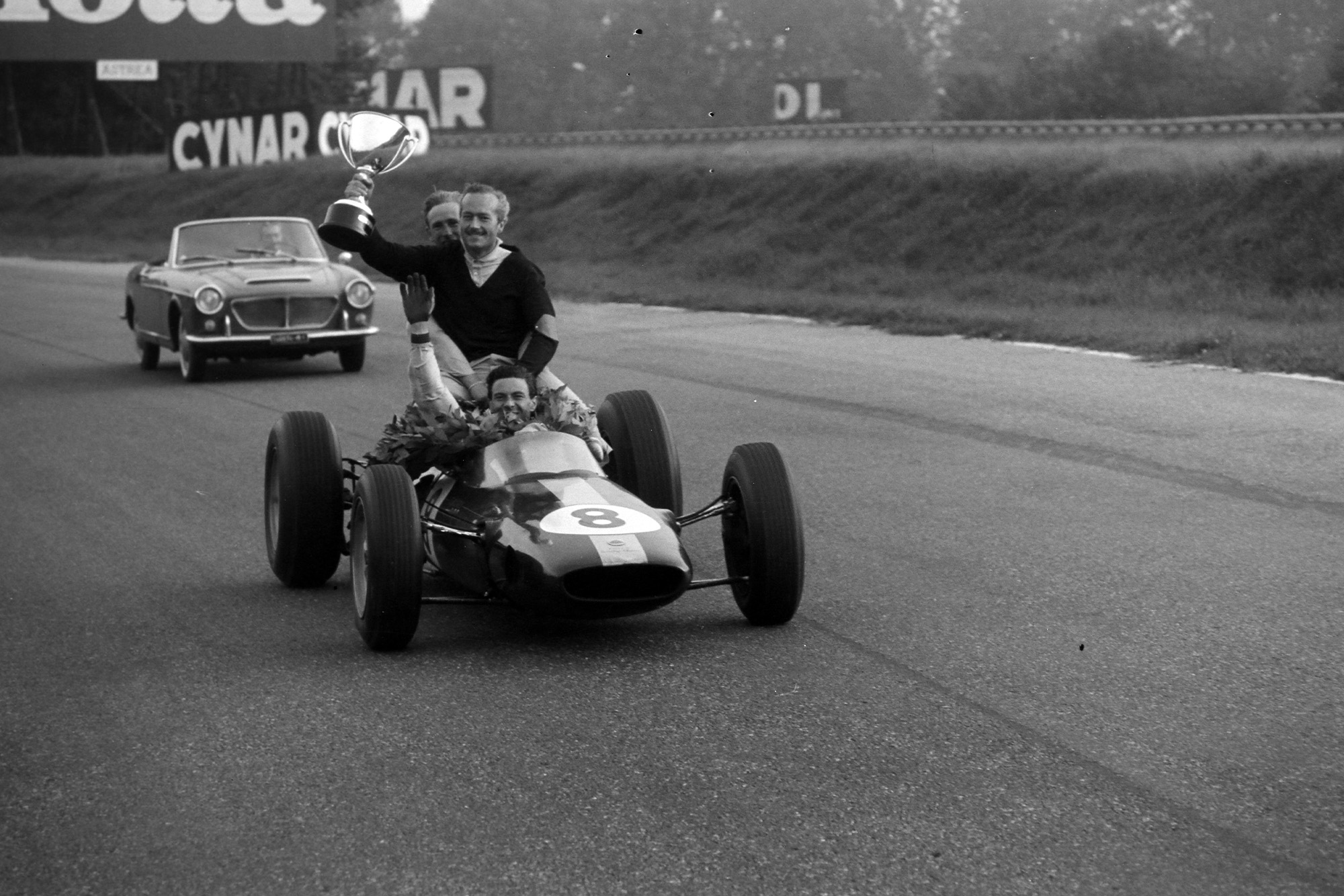 Jim Clark, Lotus 25 Climax, with Colin Chapman holding the winner's trophy on the back.