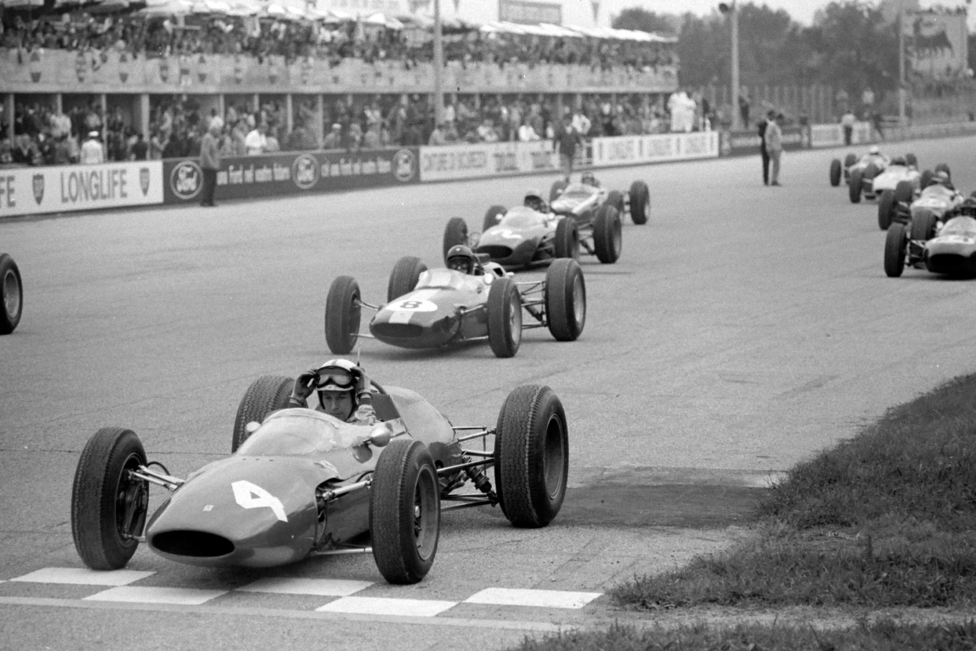 John Surtees, Ferrari 156 Aero, Jim Clark, Lotus 25 Climax, Lorenzo Bandini, Ferrari 156/63, Dan Gurney, Brabham BT7 Climax, and the rest of the field on the grid awaiting the start.