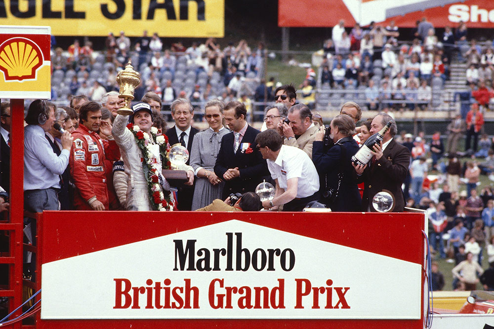 Alan Jones (Williams Ford) celebrates his 1st position on the podium. TRH Prince and Princess Michael of Kent stand to the right and Carlos Reutemann (Williams Ford) 3rd position and commentator Brian Jones to the left.