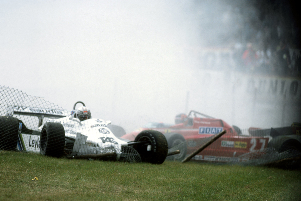 L-R: Alan Jones (Williams FW07C) becomes a victim of the catch fencing after getting caught up in the accident of Gilles Villeneuve, (Ferrari 126CK).