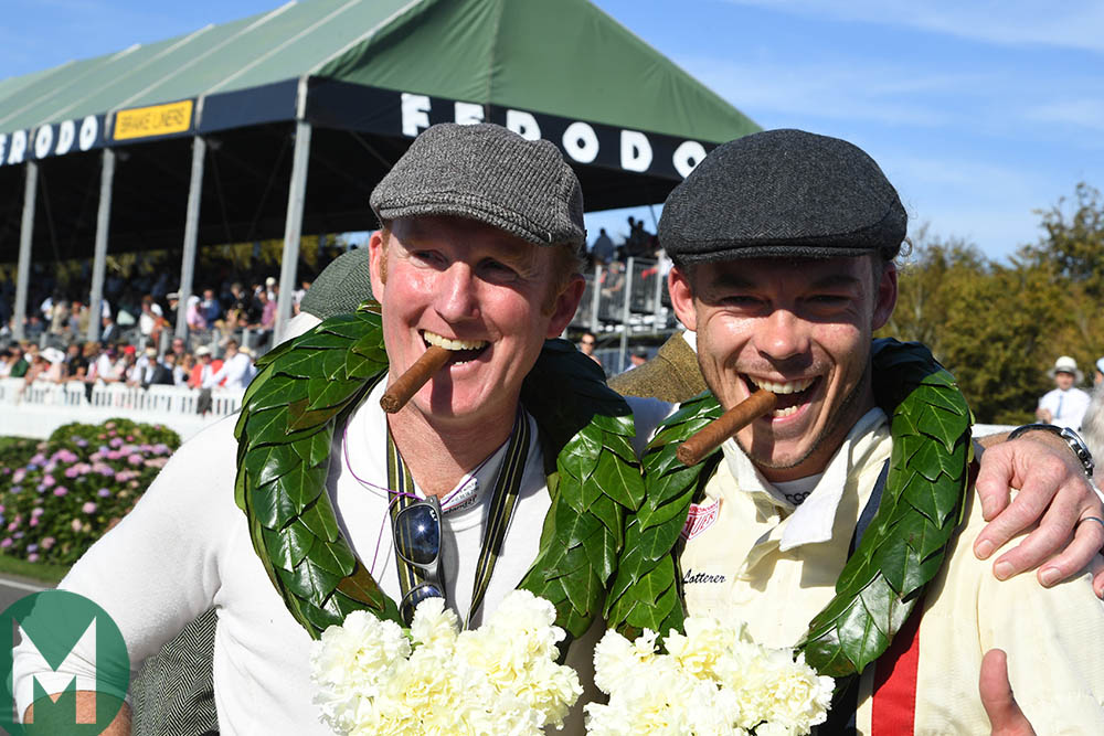 Andre Lotterer and Christopher Wilson, cigars in mouths, celebrating their victory in the RAC TT race at the 2019 Goodwood Revival