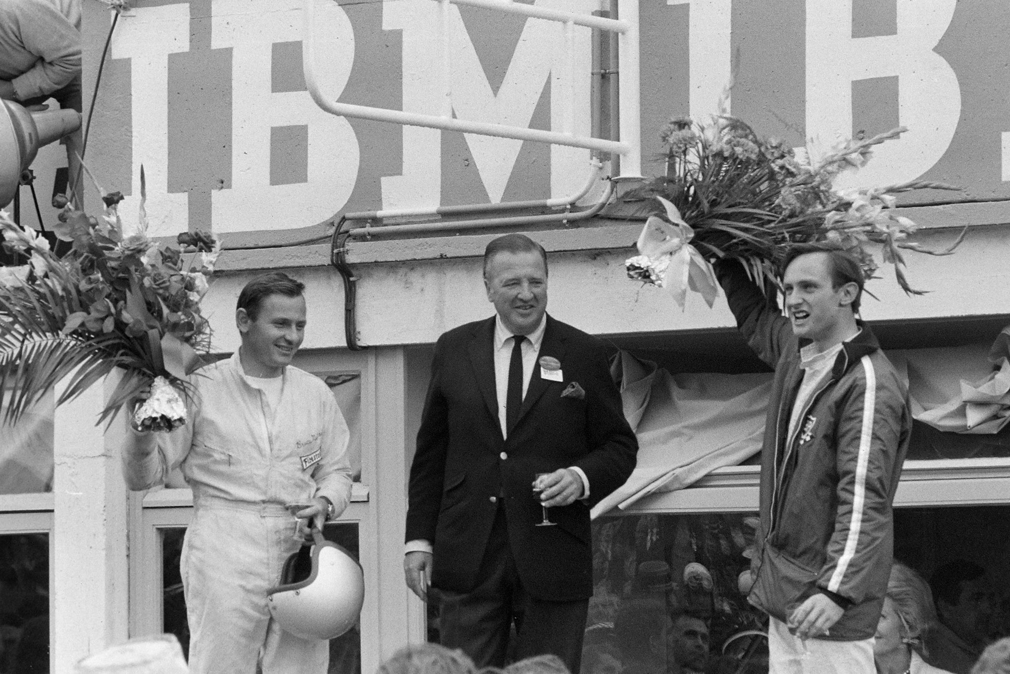 Henry Ford II stands on the podium alongside Bruce McLaren and Chris Amon