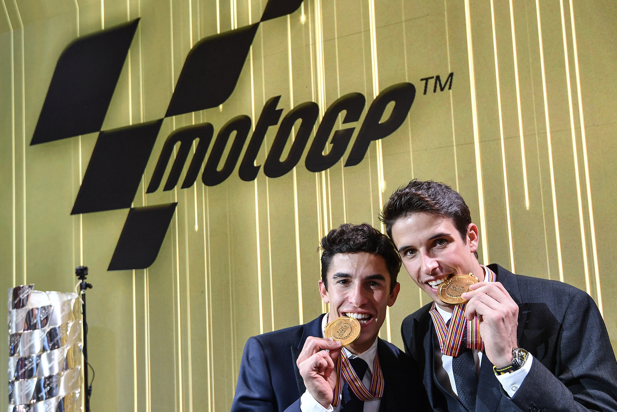 Marc Marquez and Alex Marquez bite their MotoGP and Moto2 championship medals for the camewras