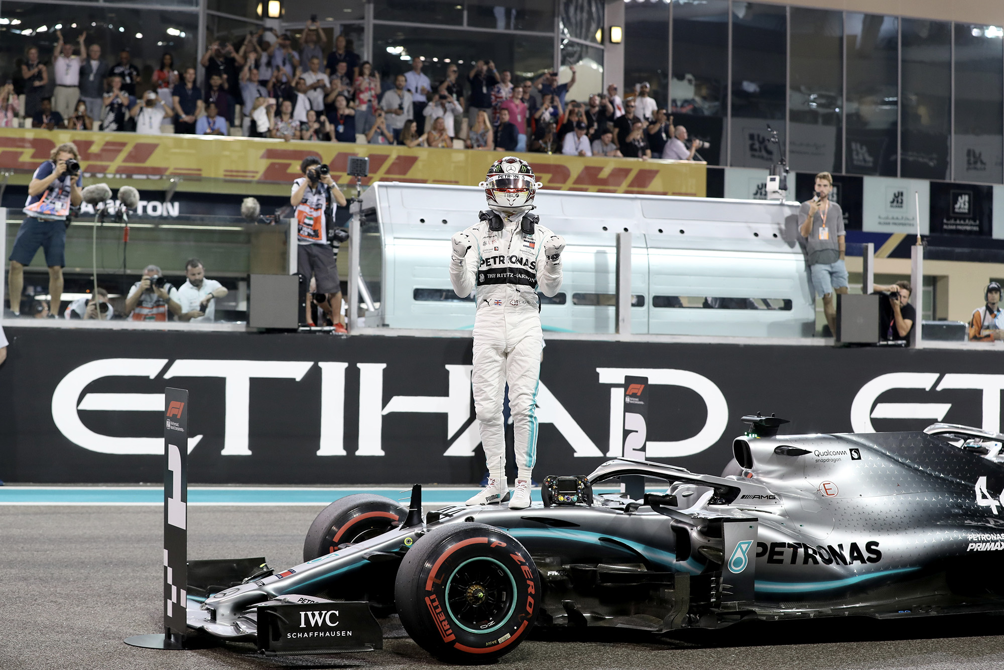 Lewis Hamilton stands on his Mercedes as he celebrates taking pole position for the 2019 Abu Dhabi Grand Prix