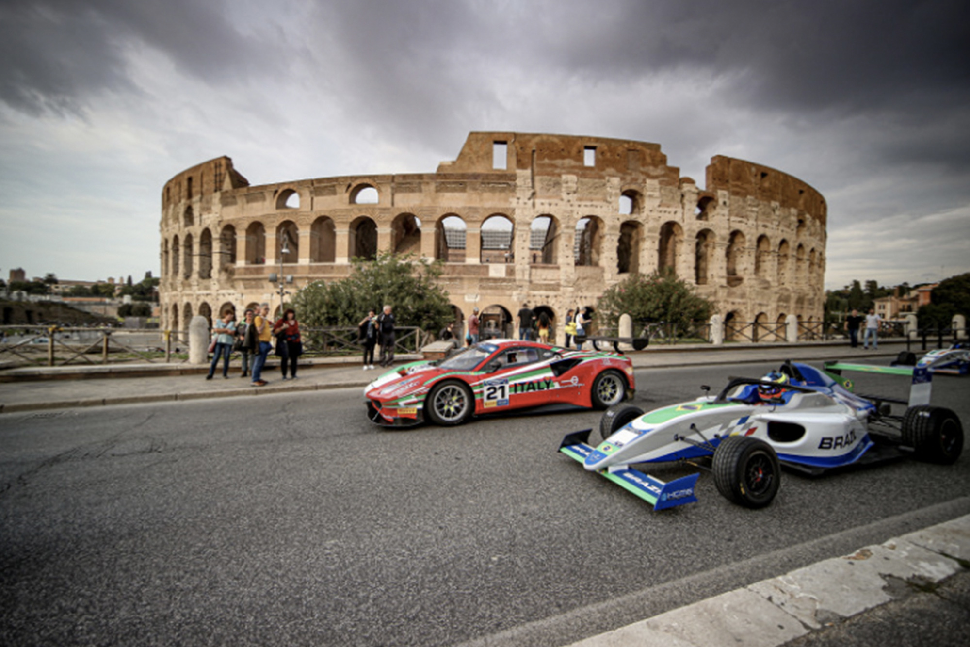 A single-seater and GT car drives in front of Rome's Colosseum ahead of the 2019 Motorsport Games
