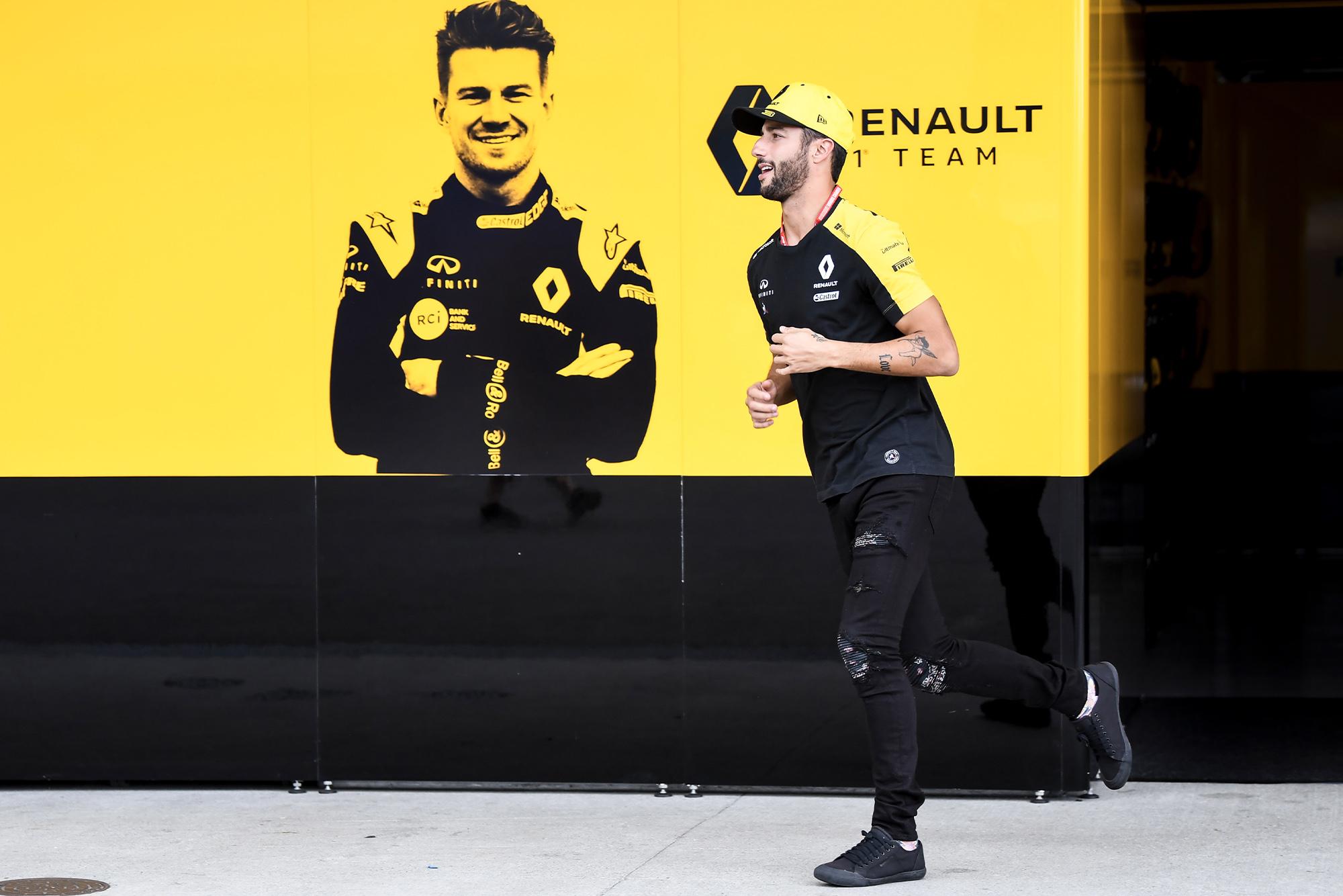 Daniel Ricciardo runs past a board showing his Renault team-mate Nico Hulkenberg