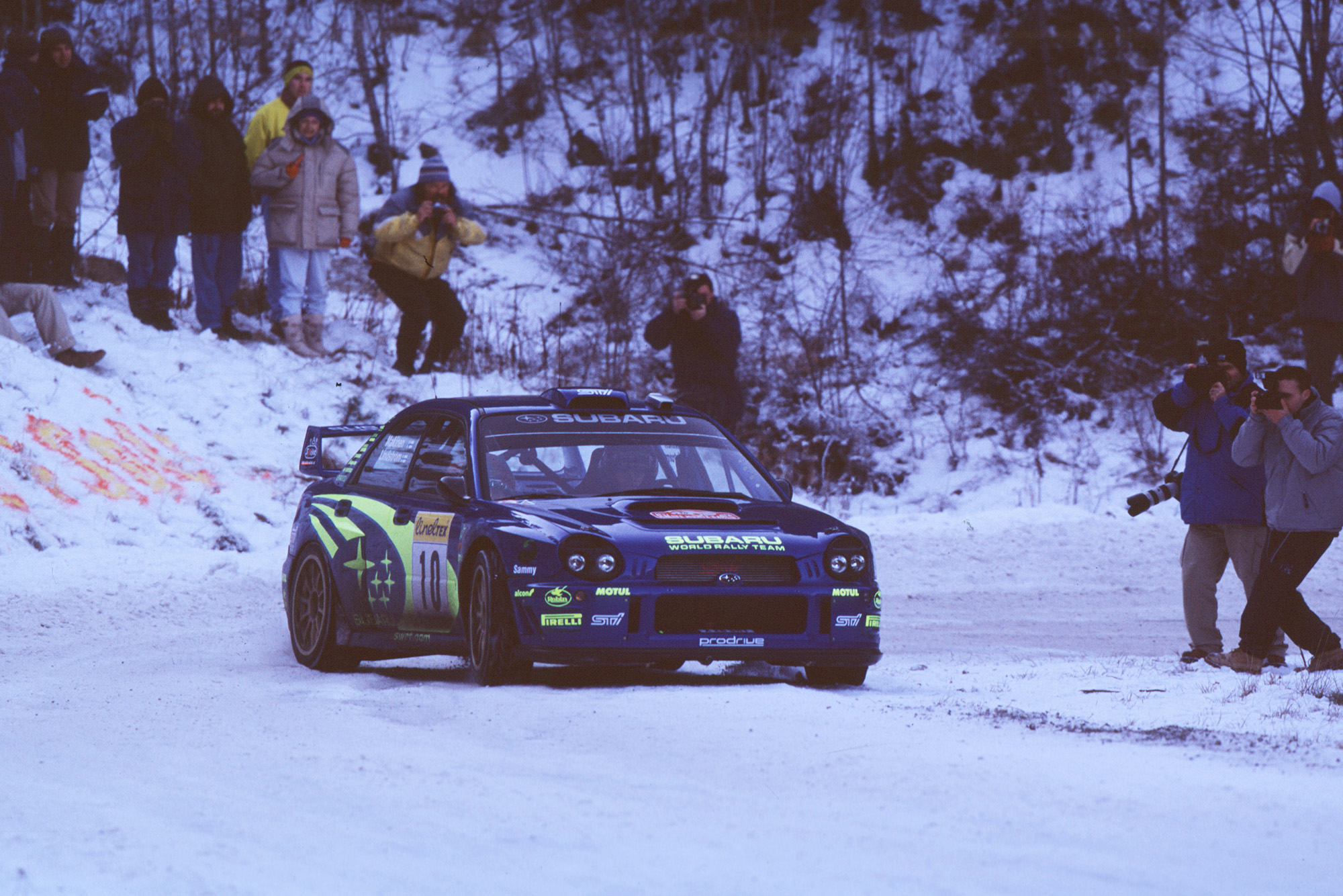 Subaru's Tommi Mäkinen slides past spectators during the 2002 Monte Carlo Rally