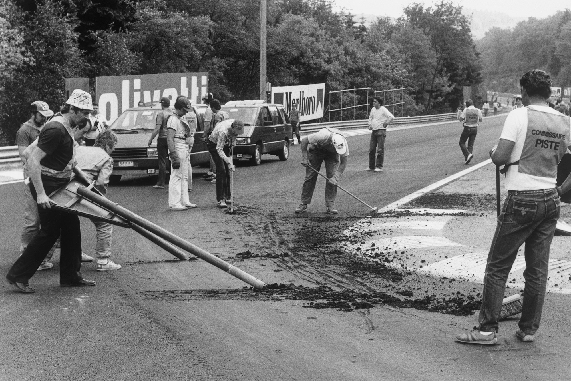 Workers try to repair the broken track surface ahead of the cancelled 1985 Belgian grand Prix
