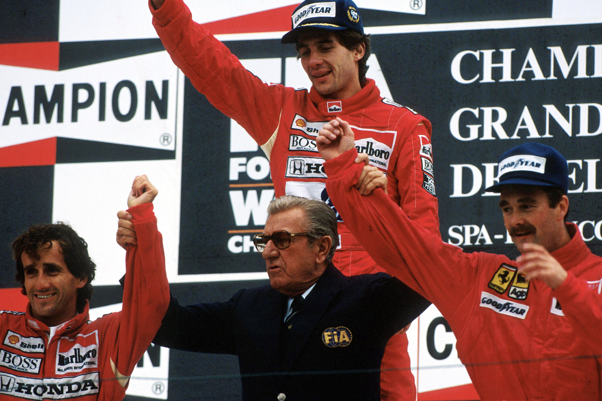 Jean Marie Balestre raises the arms of Nigel Mansell and Alain Prost in front of race winner Ayrton Senna at the 1989 Belgian Grand Prix