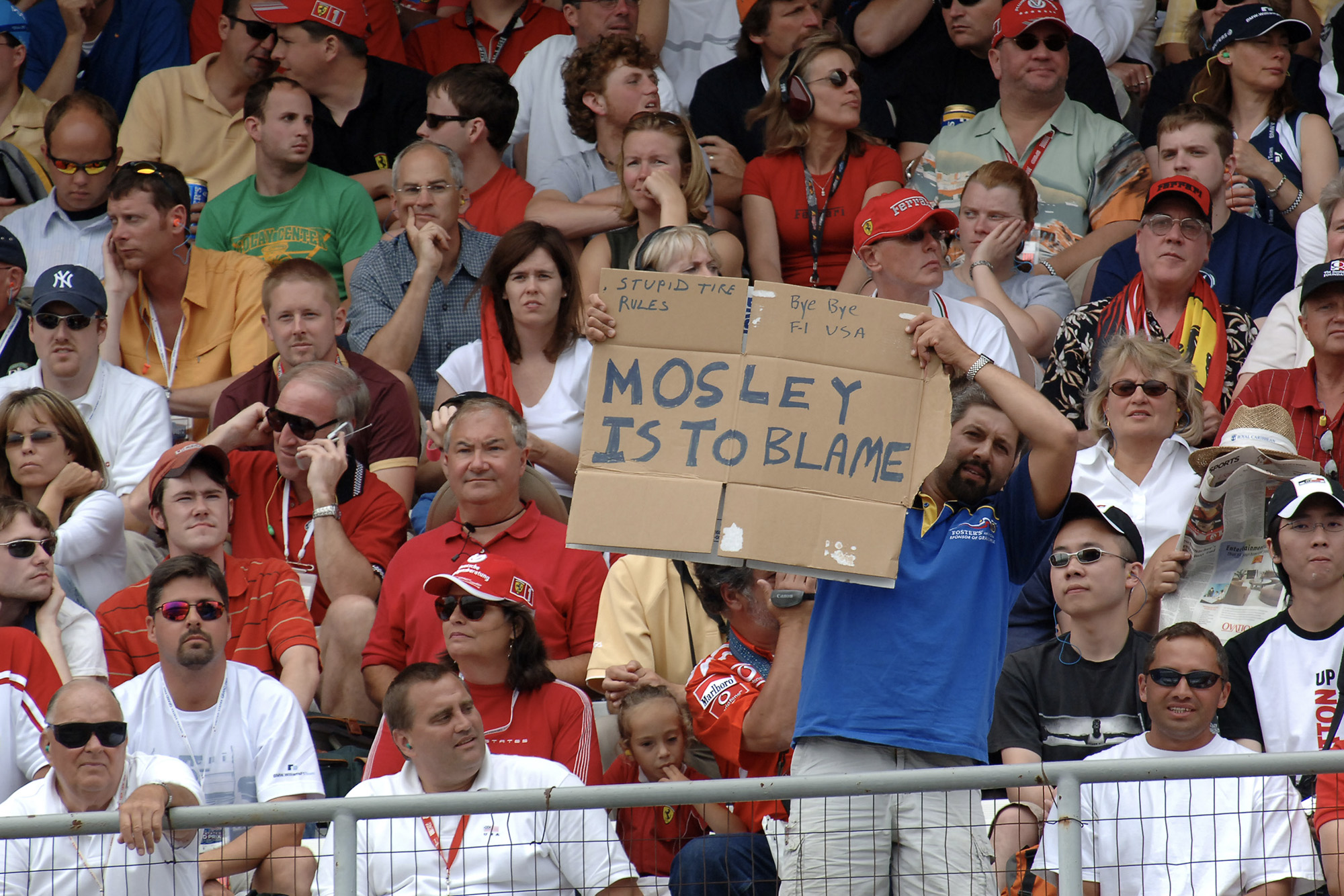 A fan holds up a Mosley is to blame sign at the 2005 United States Grand Prix