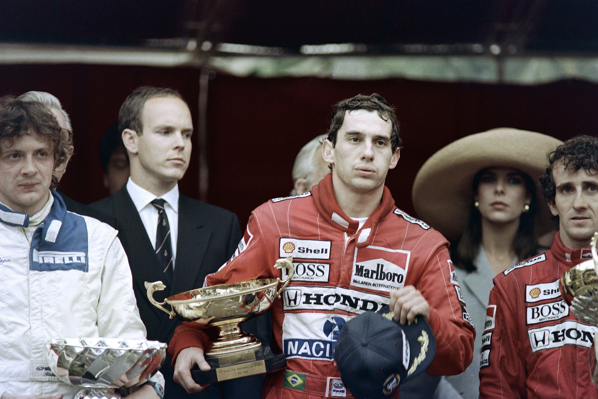 An exhausted Ayrton Senna clutches his trophy after winning the 1989 Monaco Grand Prix