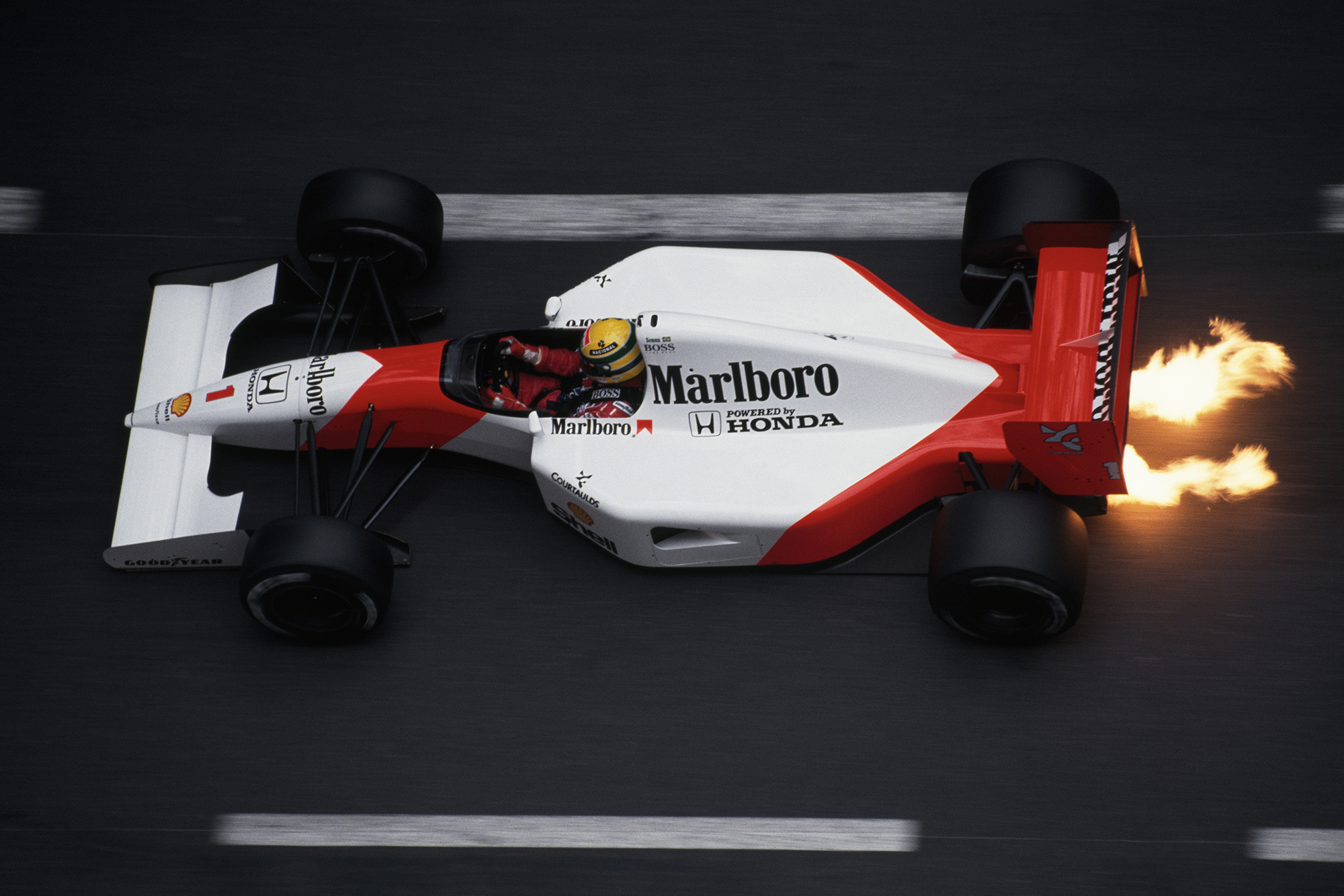Flames shoot from underneath Ayrton Senna's McLaren Honda at the 1991 Monaco Grand Prix