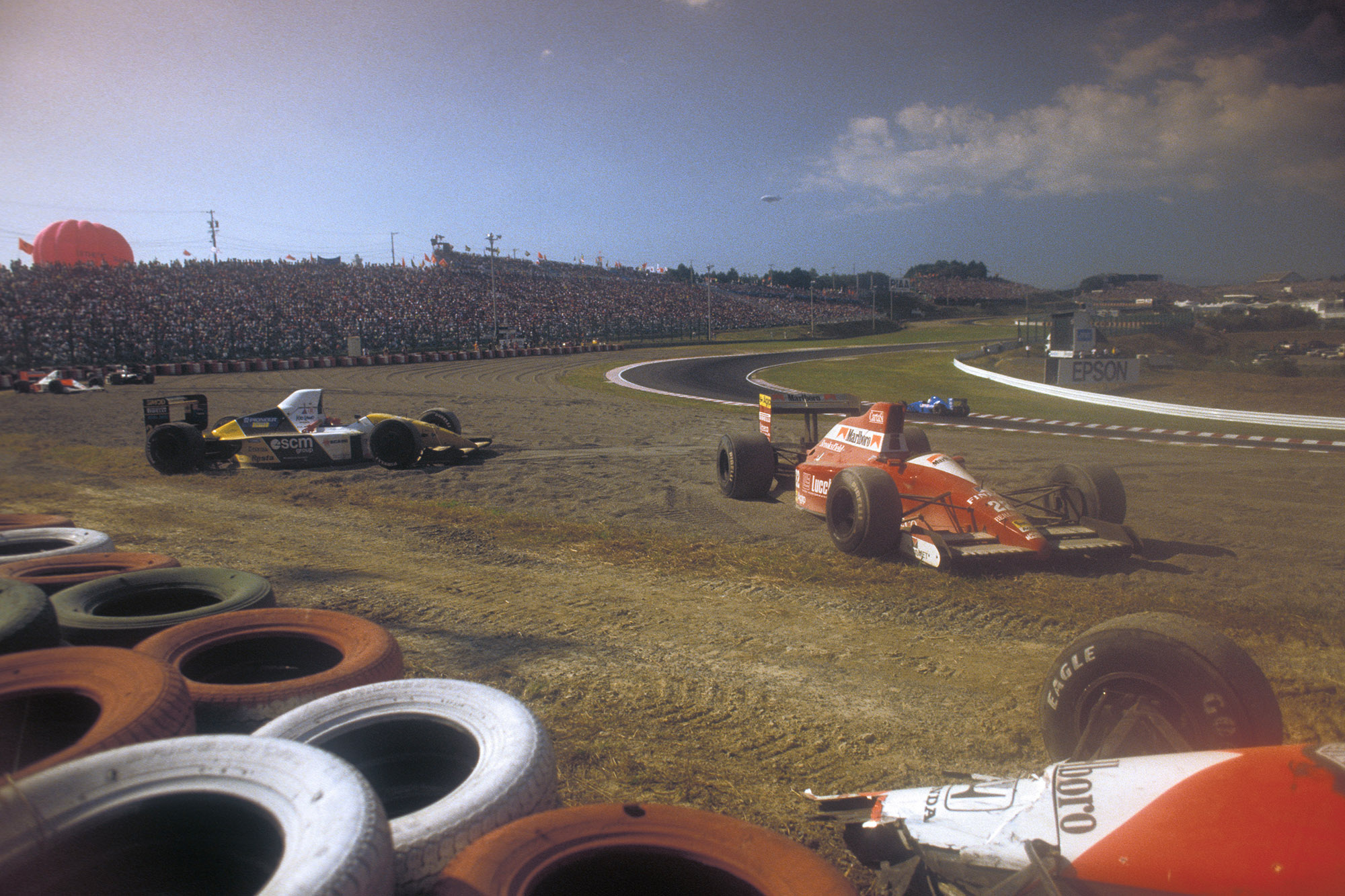 Crashed cars litter the side of the track after the first corner crash at the 1990 Japanese Grand Prix