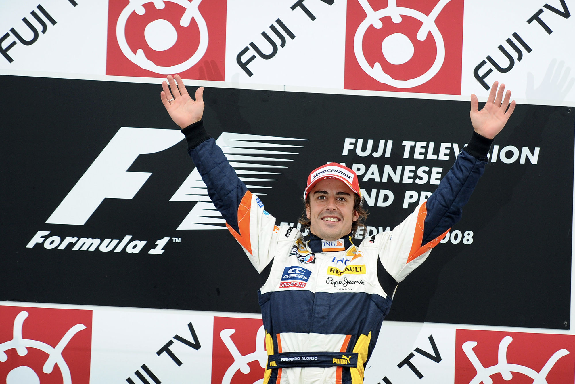 Fernando Alonso celebrates victory on the podium at the 2008 Japanese Grand Prix