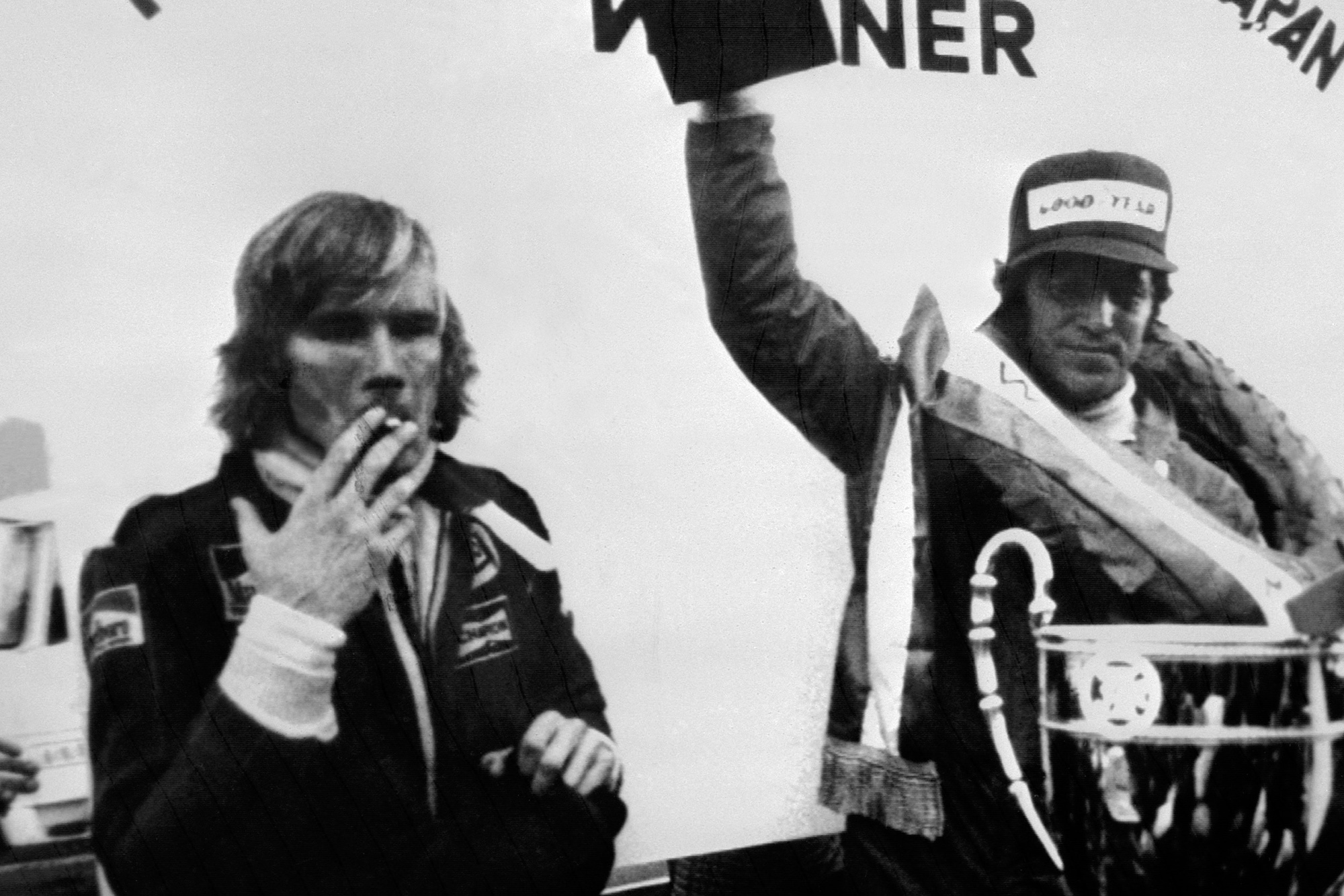 James Hunt smokes a cigarette as Mario Andretti celebrates winning the 1976 Japanese Grand Prix