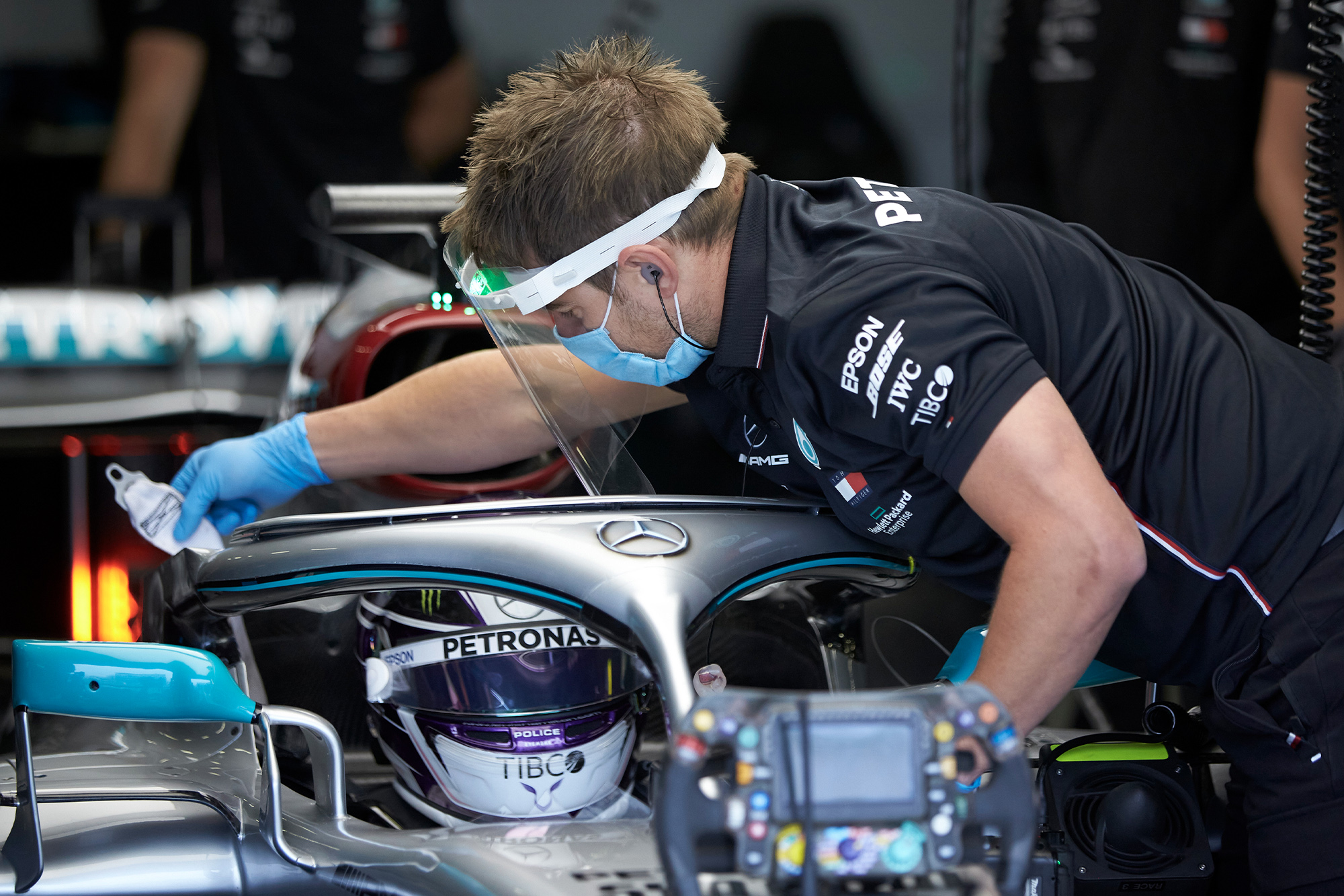 Lewis Hamilton is strapped in to his MErcedes by a man wearing a mask and visor at a 2020 Silverstone test