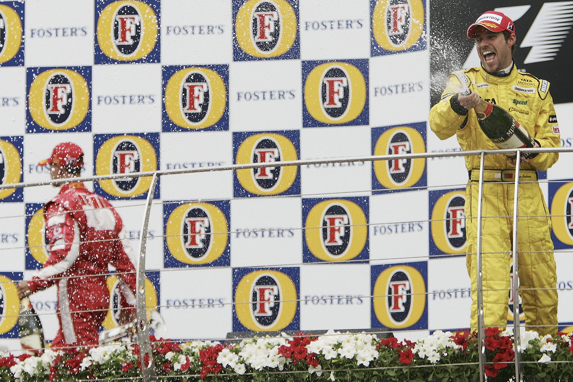 Tiago Monteiro sprays champagne as Michael Schumacher walks off the podium at the 2005 US Grand Prix