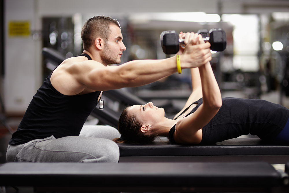 woman lifting weights with male spotter