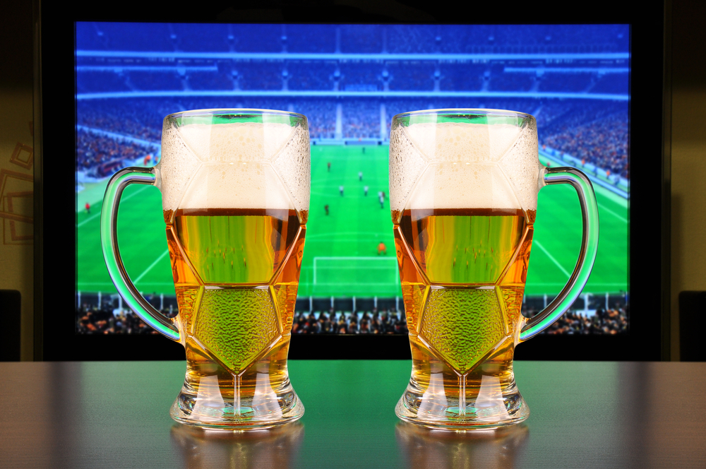 Glasses of beer in front of Football on TV
