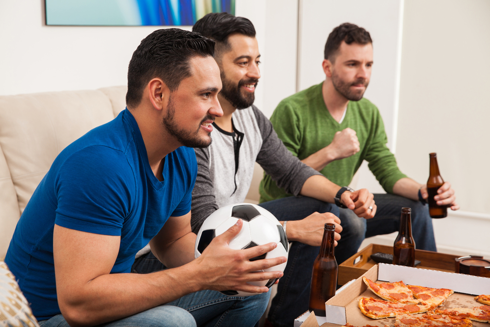 People drinking beer and eating pizza while watching football
