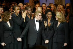 Yves Saint Laurent entouré de Laetitia Casta, de Catherine Deneuve et de ses mannequins, toutes en smoking, pour le final du défilé, Centre Pompidou, Paris, 22 janvier 2002. Photographie de Guy Marineau., © Musée Yves Saint Laurent Paris / Guy Marineau