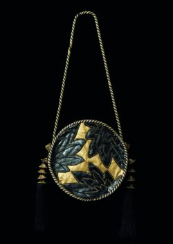 Protoype for a handbag, autumn-winter 1977 haute couture collection. Tambourine bag in gold leather decorated with black ribbed and topstitched waxed leaves and trimmed with a gold and black passementerie cord ending in two black silk tassels with gold metal ornaments shaped like small pagodas, © Yves Saint Laurent / Photos : Sophie Carre