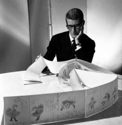 Yves Saint Laurent et les planches originales de La Vilaine Lulu, 5 juin 1964. Photographie de Robert Doisneau., © Robert Doisneau / Gamma-Rapho