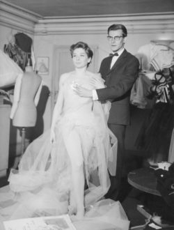 Zizi Jeanmaire and Yves Saint Laurent during a costume fitting for Roxane in the ballet Cyrano de Bergerac, House of Christian Dior, 30 avenue Montaigne, Paris, 1959. Photograph by André Ostier., © Les ayants droit d'André Ostier