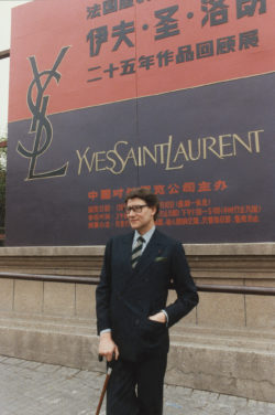 Yves Saint Laurent in front of the poster for his retrospective at the Palais des Beaux-Arts, Beijing, 1986., © Droits Réservés