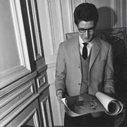 Yves Saint Laurent consulting his drawings for the televised ballet Les Forains (1961), 3 place Vauban, Paris, 1961. Photograph by Pierre Boulat., © Courtesy Association Pierre et Alexandra Boulat
