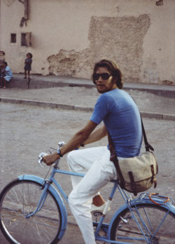 Yves Saint Laurent riding a bicycle, Morocco, 1960s. Photograph by Pierre Bergé., © Pierre Bergé