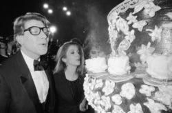 Yves Saint Laurent et Catherine Deneuve soufflant les bougies des 20 ans de la maison de couture, Cabaret Le Lido, Paris, 28 janvier 1982. Photographie de Daniel Simon., © Daniel Simon/Gamma-Rapho