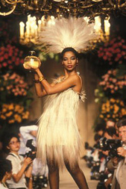 Mounia Orosemane wearing a wedding gown and carrying a bottle of the fragrance Paris at the end of the fashion show for the autumn-winter 1983 haute couture collection, Salon impérial of the Hôtel Inter-Continental, Paris, July 1983. Photograph by Guy Marineau., © Musée Yves Saint Laurent Paris / Guy Marineau
