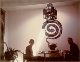 Yves Saint Laurent and Pierre Bergé in the dining room with the snake painted by the couturier, Villa dar el Hanch, Marrakech, 1960s., © Droits réservés