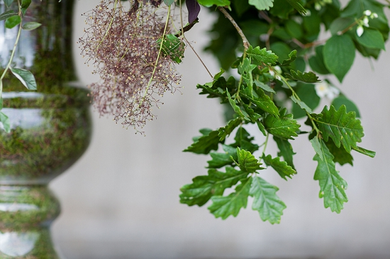 Euphoric Flowers design of arching branches of oak, eucaluptus, philadelphus, cotinus, flowering privet, aruncus and physocarpus cascade from a moss lined vase for British Flowers Week at New Covent Garden Flower Marke