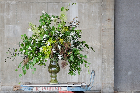 Euphoric Flowers design of arching branches of oak, eucaluptus, philadelphus, cotinus, flowering privet, aruncus and physocarpus cascade from a moss lined vase for British Flowers Week at New Covent Garden Flower Market