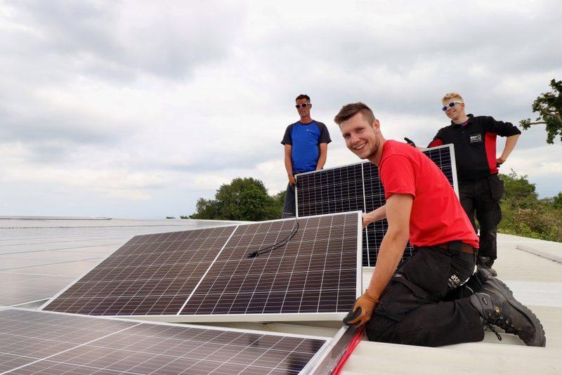 Medewerkers van ASN Installaties leggen de laatste panelen op het dak.