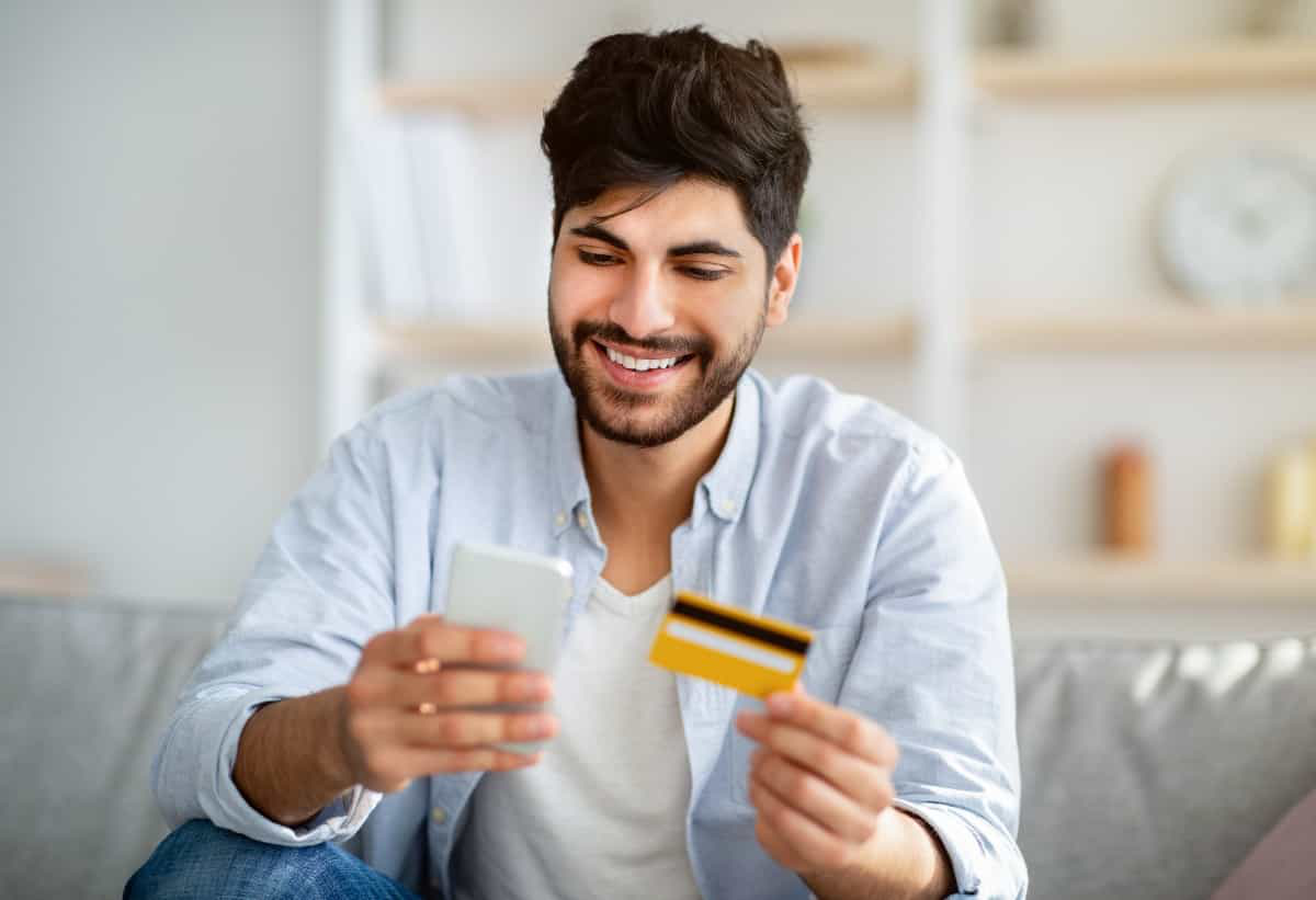 happy smartphone user making a payment over internet