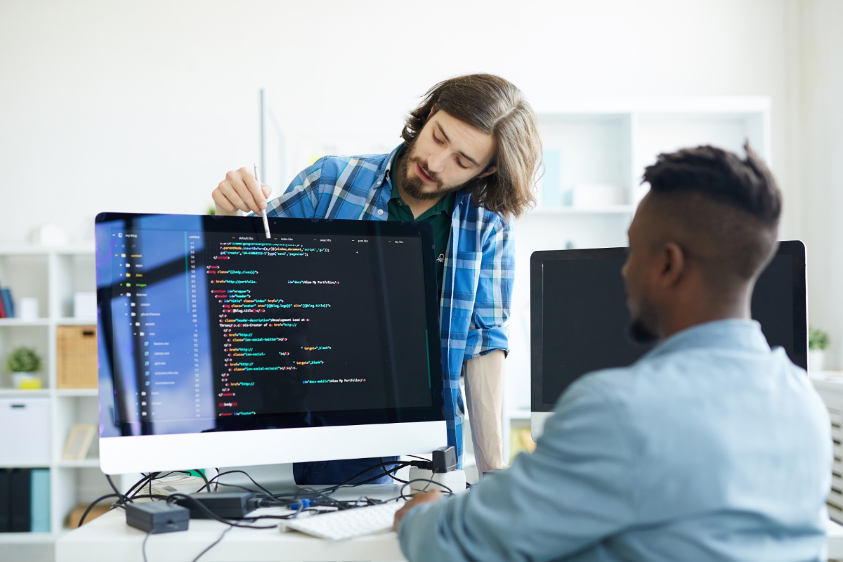 two men in office cooperating writing code