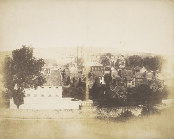 Linlithgow from above the railway line, trucks seen over a wall, houses in middle ground, Town Hall, St Michael's Church and Palace behind ...