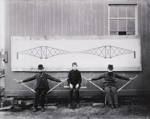The Forth Bridge. Two Seated Men Raising a Boy up to Demonstrate the Cantilever Principle