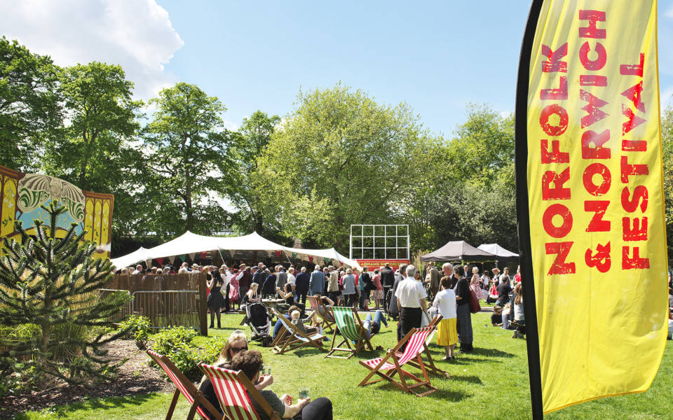 Picture taken in the Adnams Spiegeltent compound. People sit in deckchairs and other people are queuing to get into the Spiegeltent. A large yellow and red NNF flag is in the foreground of the image.